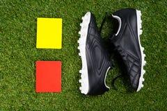 Dos tarjetas de la pena para el árbitro y los zapatos del fútbol, contra la perspectiva de la hierba imagen de archivo libre de regalías