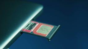 Dos tarjetas de SIM en la ranura en el teléfono celular metrajes