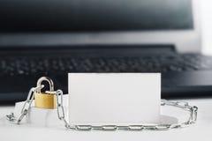 Dos tarjetas de visita blancas en el fondo de la PC, cerradura, cadena Protección del negocio y de las finanzas Protección de la  imagen de archivo