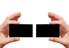 Dos tarjetas de visita negras en manos Imagenes de archivo