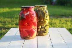 Dos tarros con los pepinos quebradizos conservados en vinagre y el tomate rojo que se colocan encendido imagenes de archivo