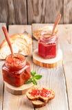 Dos tarros de cristal de atasco de la fresa y de la manzana con las cucharas y el pan cortado en la tabla de madera foto de archivo