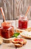 Dos tarros de cristal de atasco de la fresa y de la manzana y de pan cortado en fondo de madera foto de archivo libre de regalías