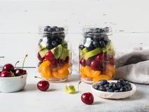 Dos tarros de cristal con las bayas y las frutas Ensalada de fruta con los albaricoques, el kiwi, las cerezas y los arándanos en  imágenes de archivo libres de regalías