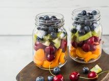 Dos tarros de cristal con las bayas y las frutas Ensalada de fruta con los albaricoques, el kiwi, las cerezas y los arándanos en  fotografía de archivo libre de regalías
