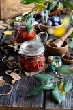 Dos tarros de cristal con los ciruelos conservados hechos en casa atascan, la mermelada, jalea en la tabla de madera rústica imagenes de archivo