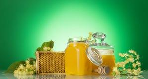 Dos tarros de cristal de la miel, del bastidor de madera con el panal y las ramas del tilo, en fondo verde Fotos de archivo