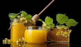 Dos tarros de cristal llenaron de la miel, del panal y de la cuchara especial aislados en negro Fotografía de archivo libre de regalías