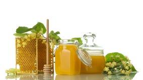 Dos tarros de miel, marcos con los panales y cuchara, al lado de las flores del tilo, aisladas en blanco Imagen de archivo