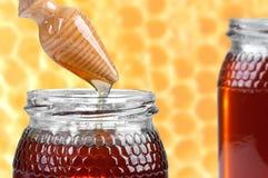Dos tarros de miel, y de drizzler de madera Imágenes de archivo libres de regalías