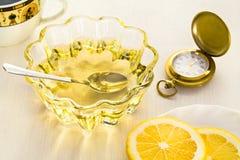 Dos taza de cristal amarilla del limón y de la miel con el reloj Imagen de archivo libre de regalías