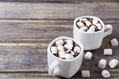Dos tazas blancas con el chocolate caliente y la melcocha en la tabla de madera lamentable Imagen de archivo
