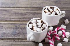 Dos tazas blancas con el chocolate caliente y la melcocha en la tabla de madera lamentable Imágenes de archivo libres de regalías