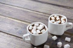 Dos tazas blancas con el chocolate caliente y la melcocha en la tabla de madera lamentable Fotos de archivo libres de regalías
