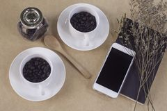 Dos tazas blancas con los granos de café, cuaderno, cuchara, teléfono móvil Imagen de archivo