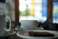 Dos tazas blancas de café y de un pedazo de brownie se apelmazan en una placa en la tabla de madera Fotografía de archivo