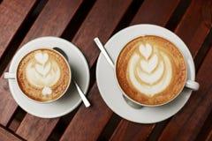 Dos tazas blancas de capuchino con arte del latte Fotografía de archivo libre de regalías