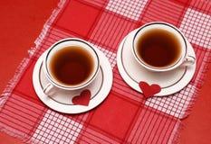 Dos tazas blancas de té con el día de tarjeta del día de San Valentín de los corazones Fotografía de archivo