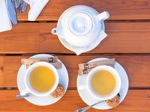 Dos tazas blancas de té y cucharas con las galletas Fotografía de archivo