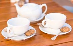 Dos tazas blancas de té y cucharas con las galletas Imagen de archivo libre de regalías