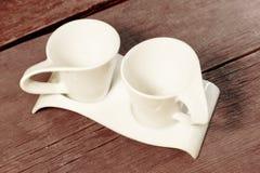 Dos tazas blancas del vintage en la tabla de madera sucia Fotos de archivo libres de regalías