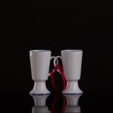 Dos tazas blancas en el asociado con una cinta roja foto de archivo