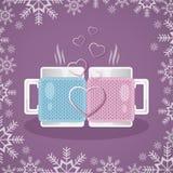 Dos tazas blancas en las cubiertas hechas punto, llenadas de una bebida caliente, se colocan enfrente de uno a En el primero plan Fotografía de archivo