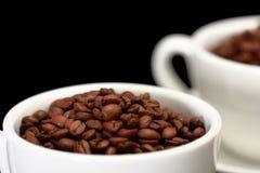 Dos tazas blancas, llenas de granos de café Fotografía de archivo libre de regalías