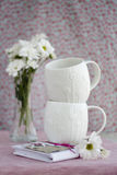 Dos tazas blancas, offlowers de un ramo y cuaderno Imagenes de archivo