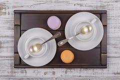 Dos tazas blancas vacías para las tortas del café o del té y del macaron en la bandeja en la tabla de madera blanca Concepto de l Imágenes de archivo libres de regalías