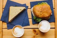 Dos tazas con café en una superficie de madera Mentira próxima un bocadillo y una hamburguesa Alimentos de preparación rápida Foto de archivo libre de regalías
