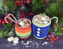 Dos tazas con la bebida y la melcocha de la Navidad Fotografía de archivo libre de regalías