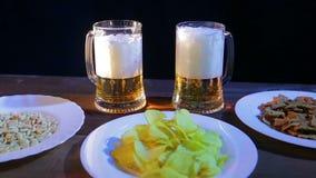 Dos tazas con la cerveza que hace espuma en una tabla de madera en una barra en un fondo negro Cerca de la placa con los micropro metrajes