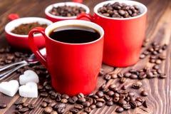 Dos tazas con la taza de café con los granos de café de madera del fondo de los granos de café alrededor de las tazas rojas Foto de archivo libre de regalías