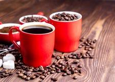 Dos tazas con la taza de café con los granos de café de madera del fondo de los granos de café alrededor de las tazas rojas Imagen de archivo libre de regalías