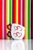 Dos tazas con los corazones en fondo colorido de las rayas Imagen de archivo