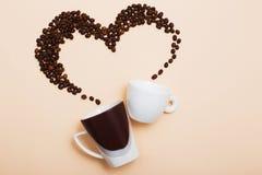 Dos tazas con los granos de café Fotos de archivo