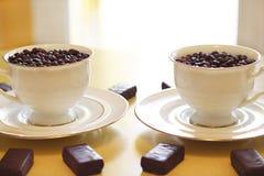 Dos tazas con los granos de café Imágenes de archivo libres de regalías