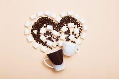 Dos tazas con los granos de café en fondo ligero Fotos de archivo