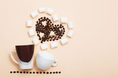 Dos tazas con los granos de café en inshape de un corazón Fotos de archivo libres de regalías