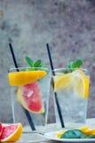 Dos tazas de agua de cristal con la naranja, el limón, la menta y el hielo rojos Franco Fotos de archivo libres de regalías