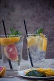 Dos tazas de agua de cristal con la naranja, el limón, la menta y el hielo rojos Franco Imagen de archivo