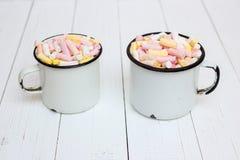 Dos tazas de cacao caliente con la melcocha del color Foto de archivo libre de regalías