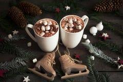 Dos tazas de cacao caliente o de chocolate caliente con las melcochas con el árbol de abeto y los patines, bebida tradicional por Imagen de archivo libre de regalías