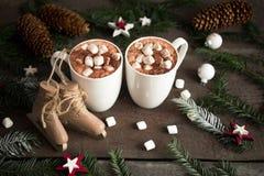 Dos tazas de cacao caliente o de chocolate caliente con las melcochas con el árbol de abeto y los patines, bebida tradicional por Foto de archivo