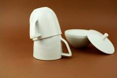 Dos tazas de café al revés con el cuenco de azúcar broncean el fondo Imagen de archivo libre de regalías