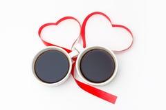 Dos tazas de café atadas con una cinta roja en la forma de corazones en un fondo blanco Fotos de archivo