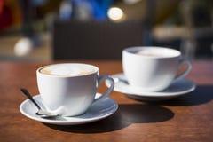 Dos tazas de café blancas en la tabla de madera imágenes de archivo libres de regalías
