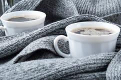 Dos tazas de café blancas envueltas en bufanda Foto de archivo libre de regalías