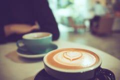 Dos tazas de café caliente en el café, uno con arte del latte de la forma del corazón Imagen de archivo